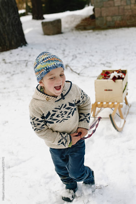 Child towing  sled load with christmas ornaments in a snowy yard by Miquel Llonch for Stocksy United