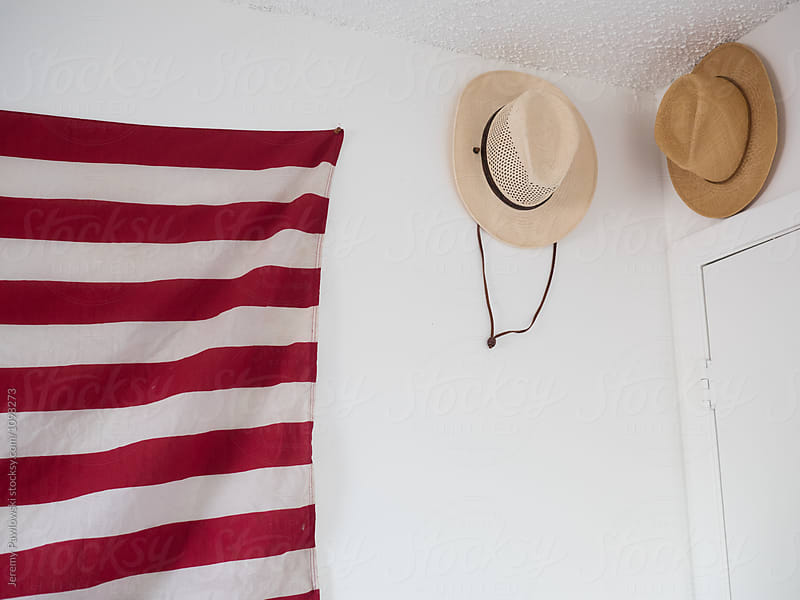 Straw hats hanging on wall of bedroom as decoration by Jeremy Pawlowski for Stocksy United