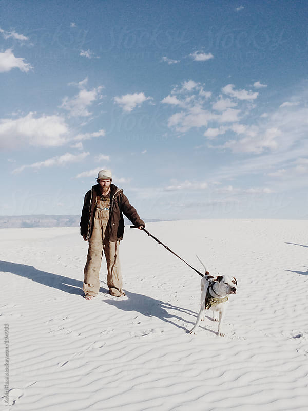 Man Holds Dog on White Sand by Kevin Russ for Stocksy United