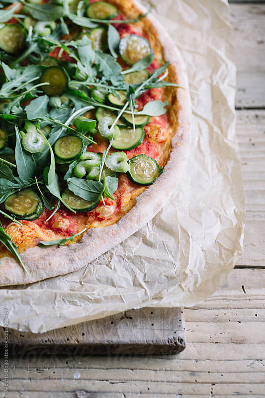 Italian pizza with courgette and arugula on wooden table by Alberto Bogo for Stocksy United