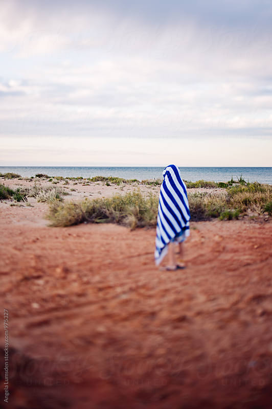 Boy wrapped in a blue and white striped towel viewed from behind, near a beach in Australia by Angela Lumsden for Stocksy United