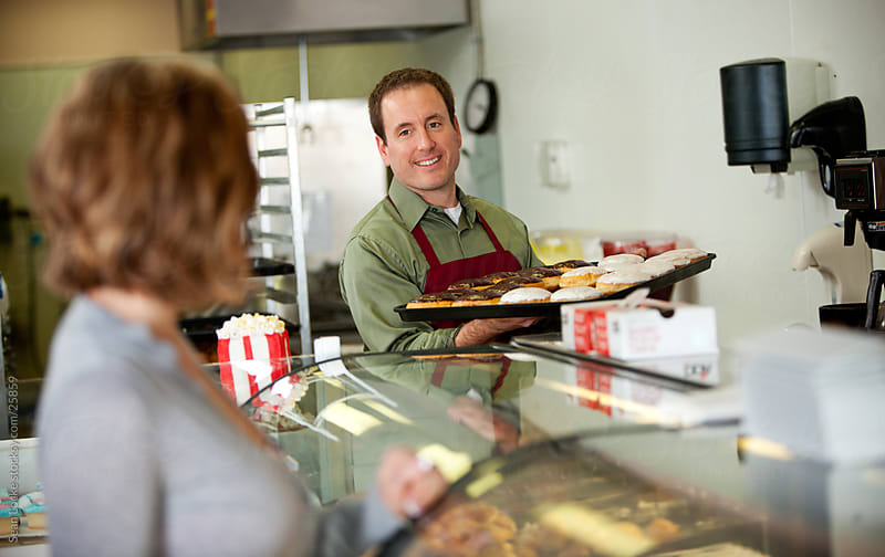 Bakery: Baker Brings Out New Tray of Donuts by Sean Locke for Stocksy United