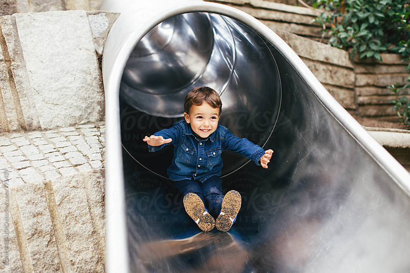 Happy kid playing on the slide.  by BONNINSTUDIO for Stocksy United