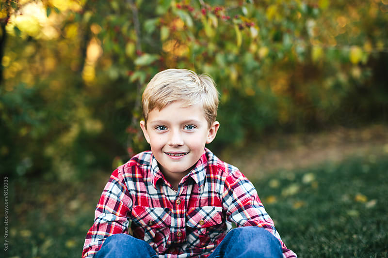 autumn portrait of a smiling boy by Kelly Knox for Stocksy United
