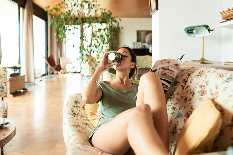 Young brunette relaxing on floral coach with magazine and drinking coffee in morning living room by Guille Faingold for Stocksy United