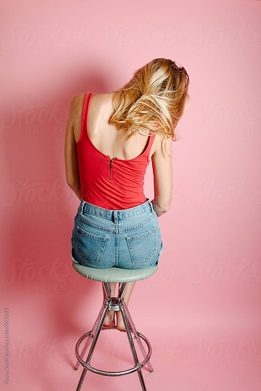 Woman sitting alone on a stool by Kayla Snell for Stocksy United