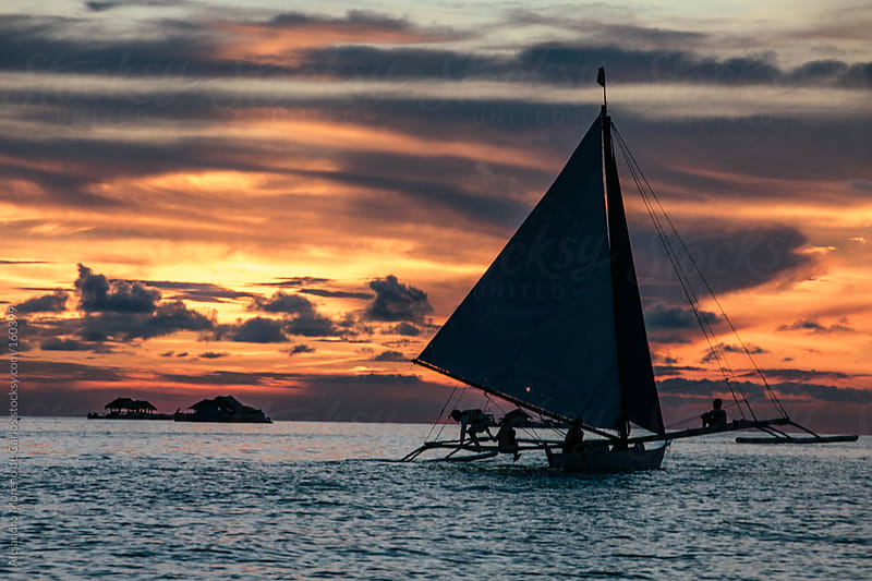 Sailboat on the sea at sunset by Alejandro Moreno de Carlos for Stocksy United