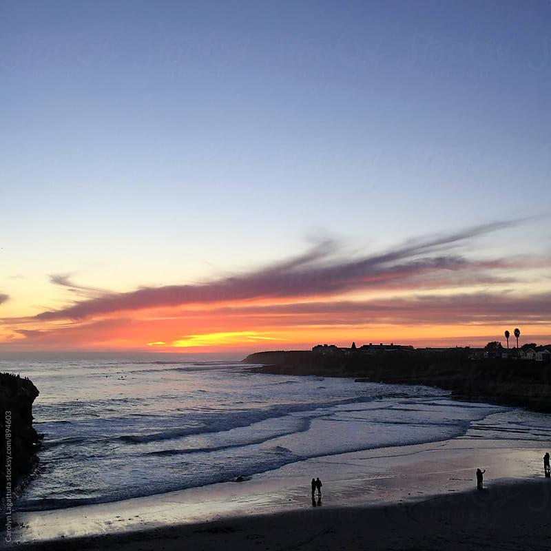 People enjoying a vibrant sunset at the beach by Carolyn Lagattuta for Stocksy United