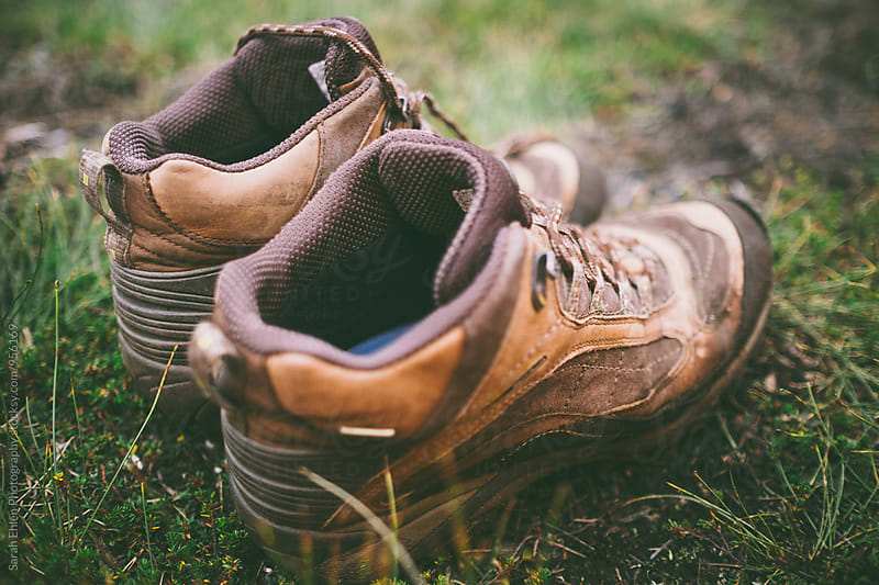 A pair of worn hiking boots sits in the grass by Sarah Ehlen Photography for Stocksy United