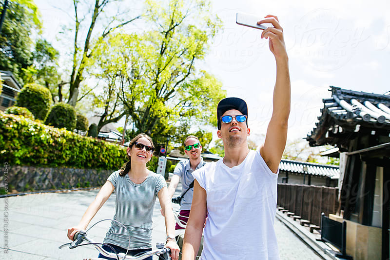 Tourist friends on bicycles taking a selfie. by BONNINSTUDIO for Stocksy United