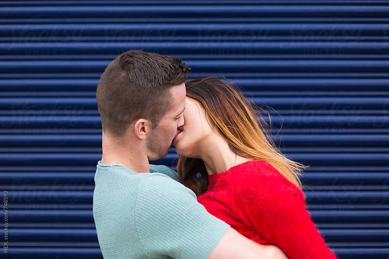 Young Couple Kissing Against a Blue Shutter by Mattia Pelizzari for Stocksy United