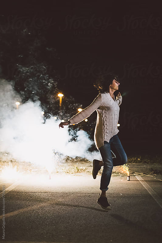 Woman enjoying fireworks outdoor at night by Mauro Grigollo for Stocksy United