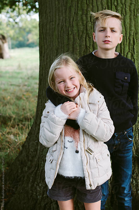 Siblings standing under a tree. by Helen Rushbrook for Stocksy United