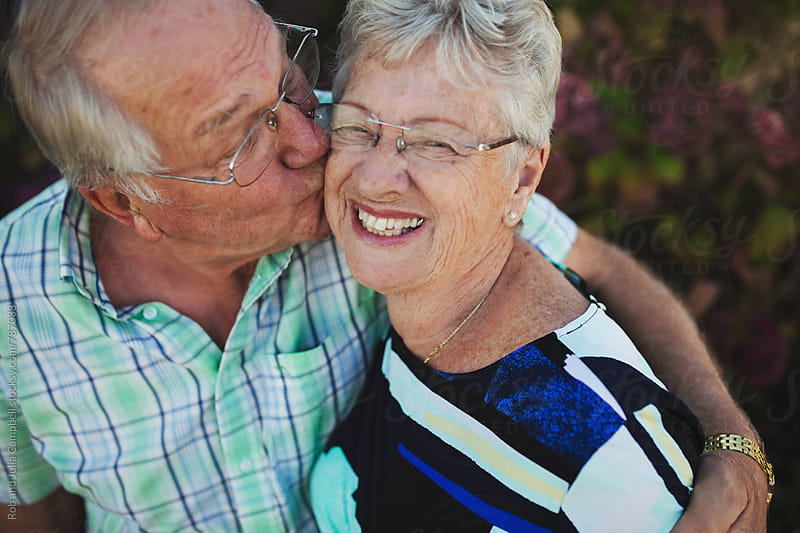 Happy senior couple outside enjoying kiss together by Rob and Julia Campbell for Stocksy United