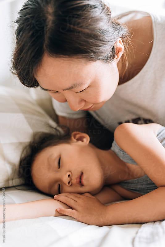Mother watching her sleeping daughter by MaaHoo Studio for Stocksy United