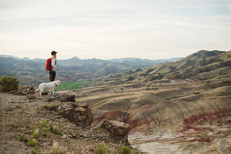 Young woman standing with white dog looking out over desert at sunrise by Kate Daigneault for Stocksy United