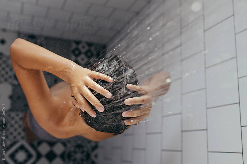 Boy under shower taking a bath. by Dejan Ristovski for Stocksy United
