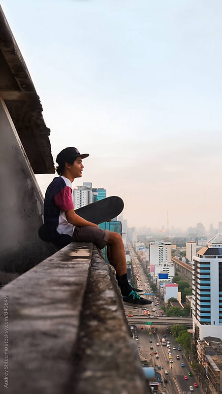Young skateboarder sitting on the roof with city below him. by Marko Milanovic for Stocksy United