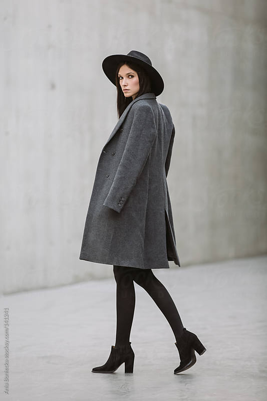 A stylish young woman taking a step looking over her shoulder by Ania Boniecka for Stocksy United