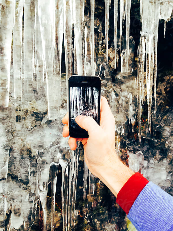 Man Holds Hand Out To Take Picture Of Icicles Using Smart Phone by Luke Mattson for Stocksy United
