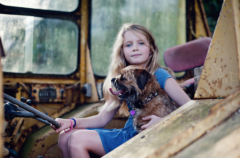 Girl and her dog in a tractor by CHRISTINA K for Stocksy United