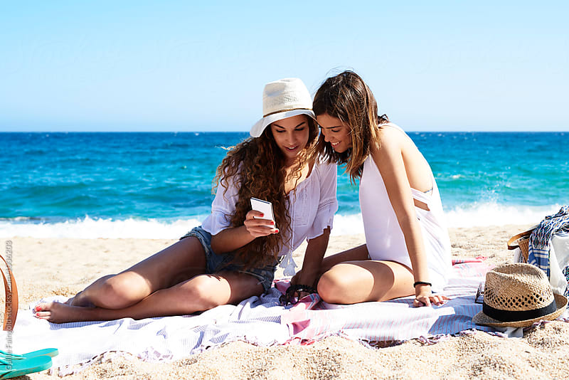 Two girlfriends on beach blanket looking at phone by Guille Faingold for Stocksy United
