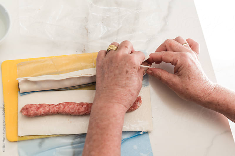 making sausage rolls at home, squeezing pastry together, brush with a little water or milk first by Gillian Vann for Stocksy United