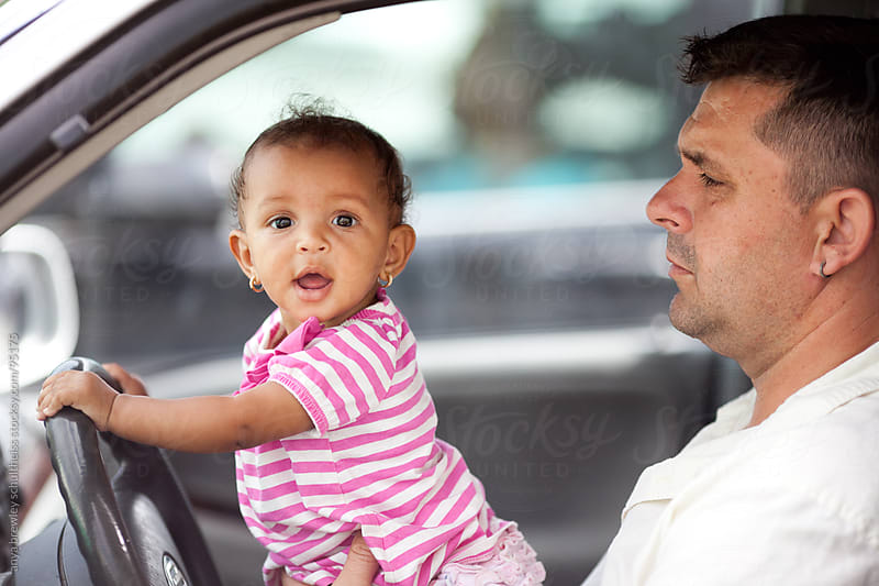 Baby girl driving with happily with her daddy by anya brewley schultheiss for Stocksy United