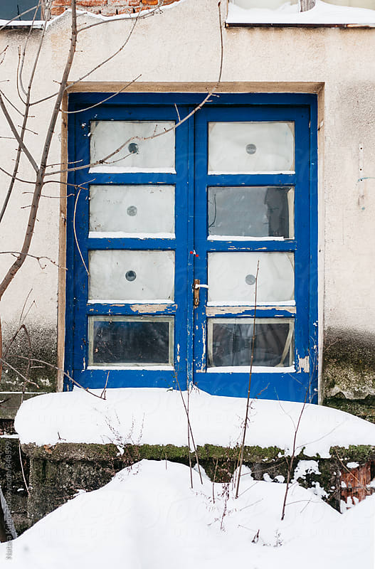 Old blue door snowed by Natasa Kukic for Stocksy United