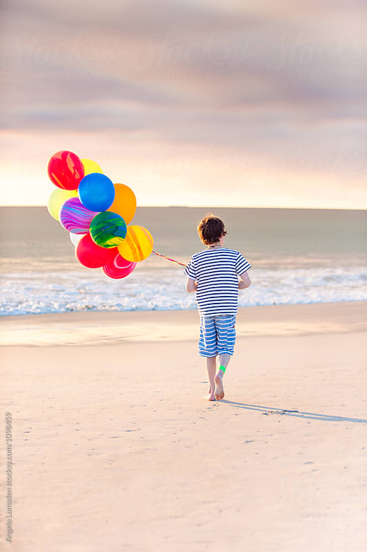 Boy with a bunch of colorful balloons walking at the beach  by Angela Lumsden for Stocksy United