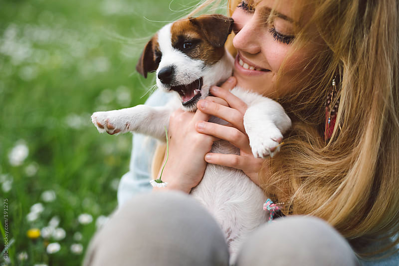 Young blonde woman having fun with a puppy on the green grass by GIC for Stocksy United