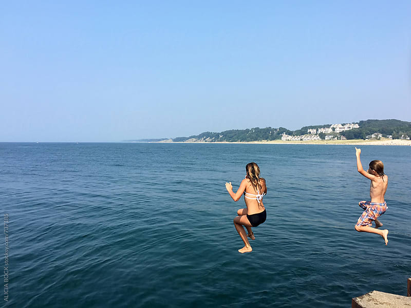 Siblings Jumping From A Pier Into A Blue Lake On A Clear Summer Afternoon by ALICIA BOCK for Stocksy United