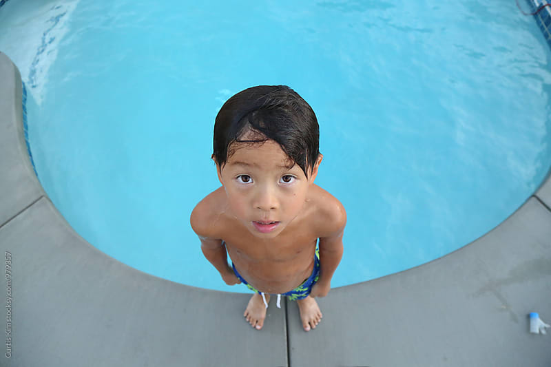 Young asian boy on the edge of pool looking up by Curtis Kim for Stocksy United
