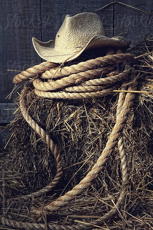 Straw hat with rope on a bale of hay in barn by Sandra Cunningham for Stocksy United