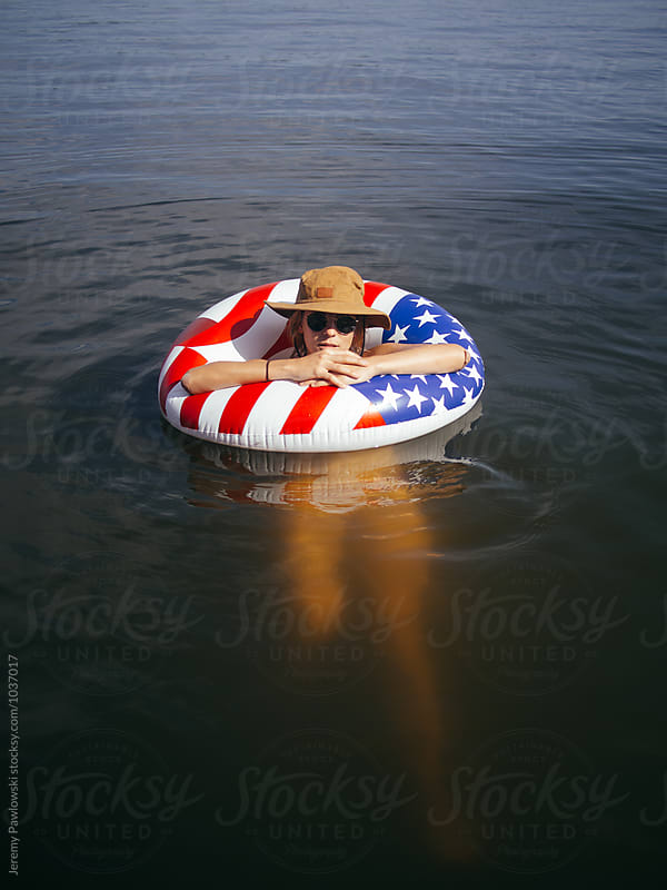 Girl relaxing in water on American Flag float by Jeremy Pawlowski for Stocksy United