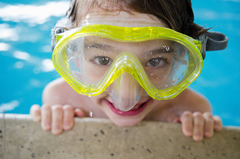 Boy in diving mask grins as he grips the edge of a swimming pool by Cara Dolan for Stocksy United