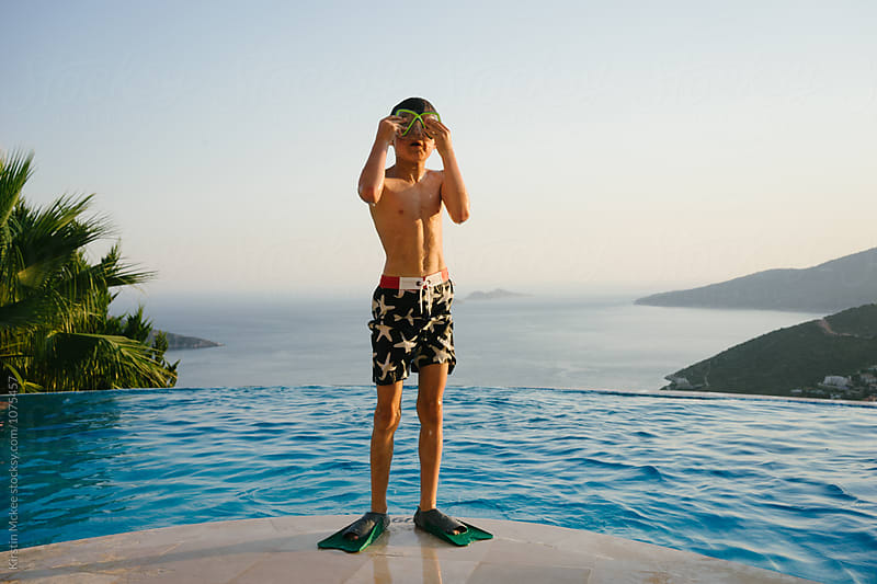 Boy putting on swimming mask before jumping into pool by Kirstin Mckee for Stocksy United