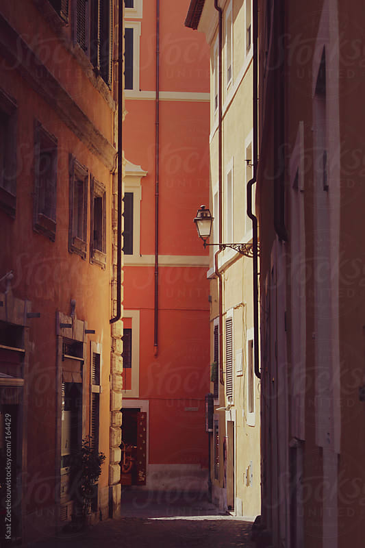 A sunlit back alley in Rome highlights the warm tones one can find in the city's architecture.  by Kaat Zoetekouw for Stocksy United