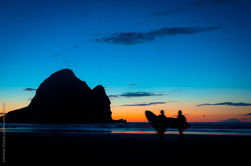 Surfer heading home on sunset by Chris Zielecki for Stocksy United