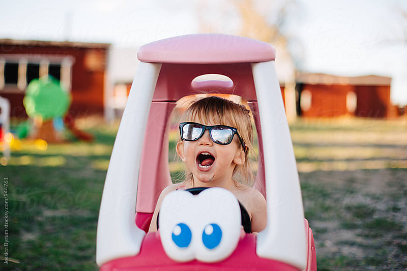 Small child making funny face in toy car by Jessica Byrum for Stocksy United