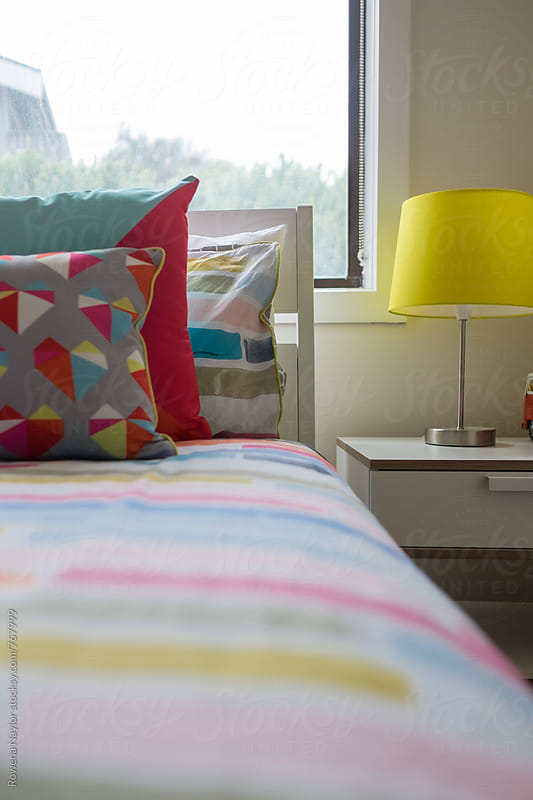Colorful cushions on bed by Rowena Naylor for Stocksy United