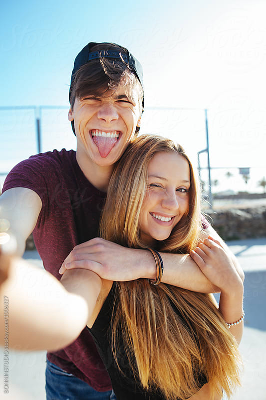 Funny teenage couple making a selfie in summer. by BONNINSTUDIO for Stocksy United