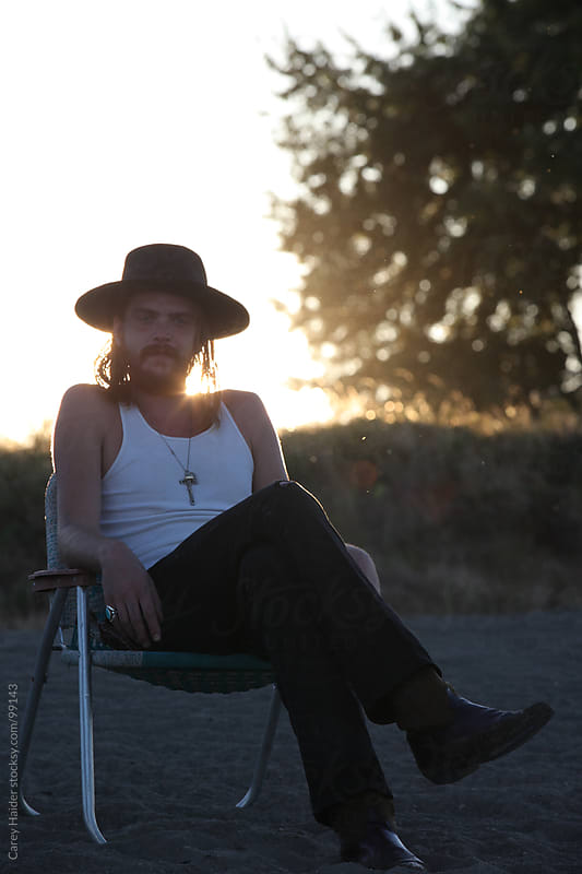 Man Sitting In A Chair At The Beach At Sundown Camping by Carey Haider for Stocksy United