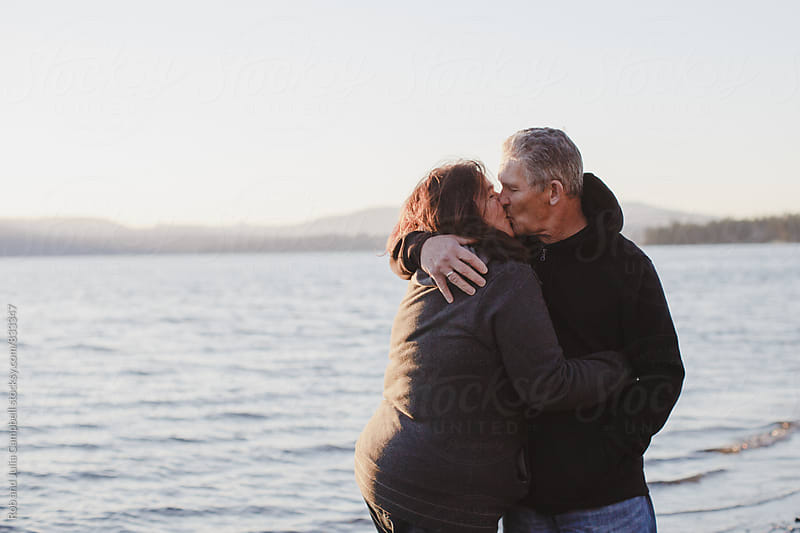 Happy, mature couple enjoying kissing each other at the beach at sunset by Rob and Julia Campbell for Stocksy United