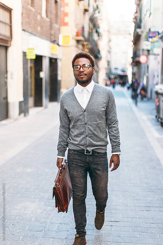 Black man walking with briefcase on Barcelona streets. by BONNINSTUDIO for Stocksy United