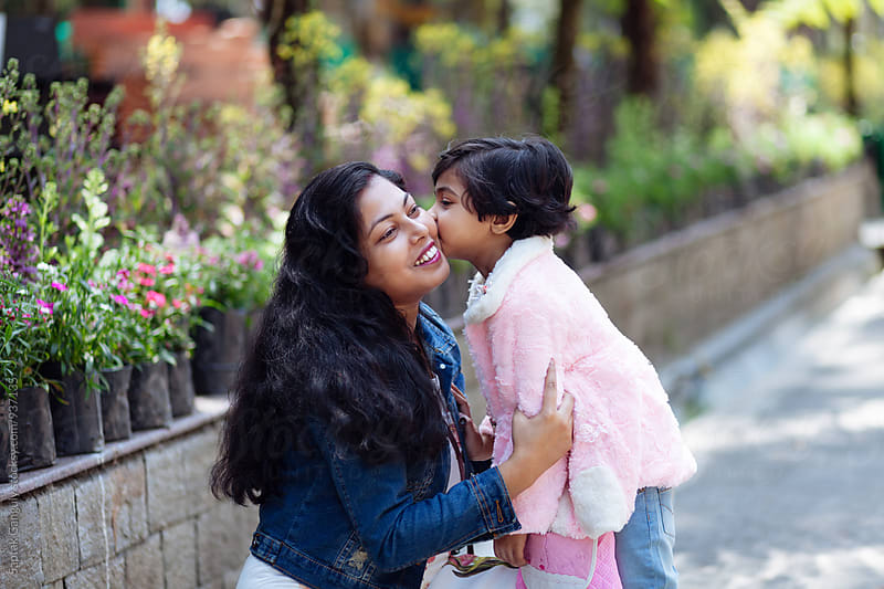 Little girl kissing her mother by Saptak Ganguly for Stocksy United