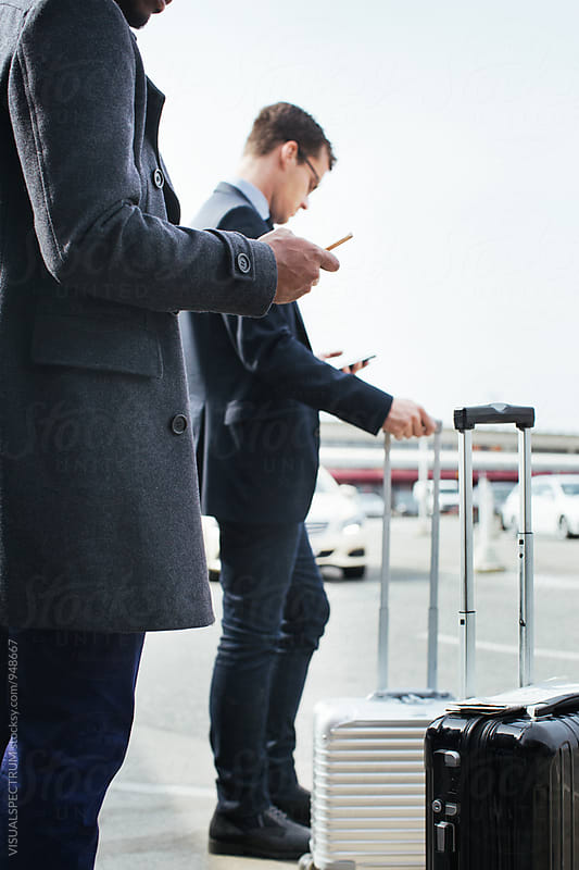 Two Business Travelers Using Cellphones as They Wait For Taxi by VISUALSPECTRUM for Stocksy United
