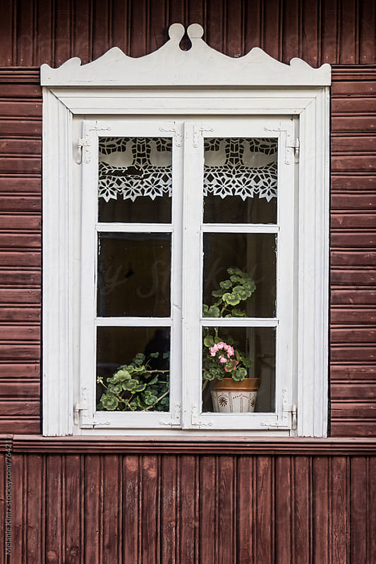 Geranium in the window of a traditional Lithuanian wooden house by Melanie Kintz for Stocksy United