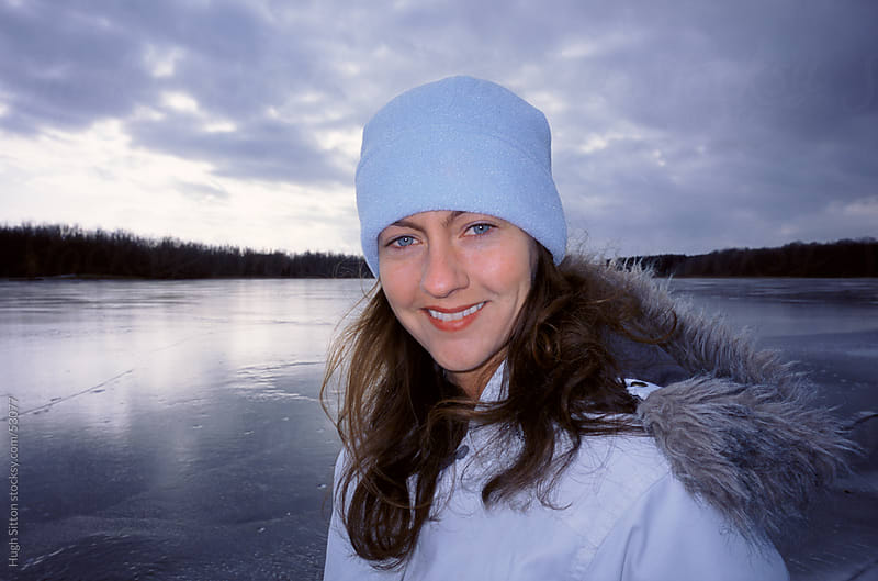 Portrait of woman standing on frozen lake. by Hugh Sitton for Stocksy United