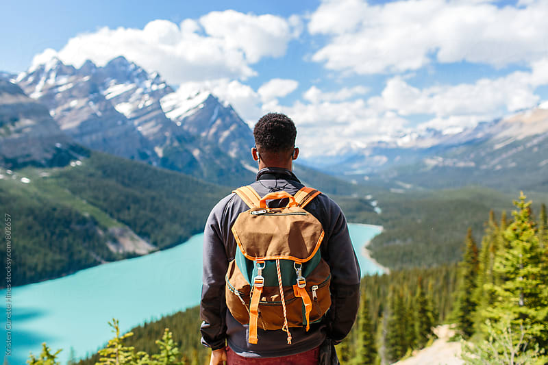 A man hiking with a backpack & looking down at moutains by Kristen Curette Hines for Stocksy United